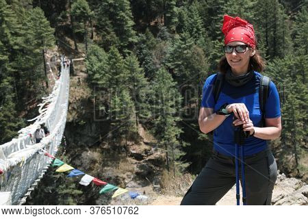 Portrait Of Hiking Woman In Sunglasses And Red Headdress Near Hillary Bridge On Thr Way To Everest B