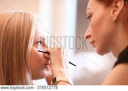 Female Makeup Artist Works With Eyes Female Model. Salon Procedure, Powder Technology. Creates Effec