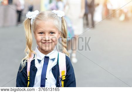 Portrait Of Cute Adorable Little Caucasian School Girl With Funny Blond Pig-tails Hair Wearing Unifo