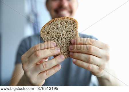Close Up Happy Guy Holds Piece Whole Grain Bread. Healthy Eating During Self-isolation. Making Homem