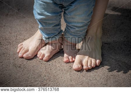 The Baby's Little Legs Are Barefoot In The Sand Next To Mom's Feet, The Baby's First Steps, Barefoot