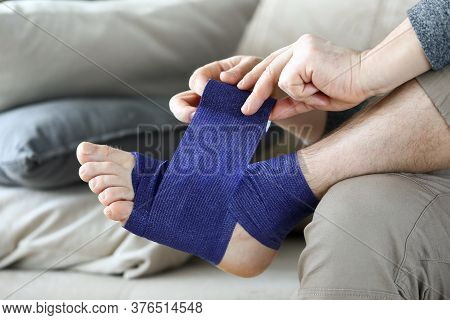 Man Sits At Home Couch And Bandages Foot Bandage. Uniform Compression All Areas For Foot Massage Eff
