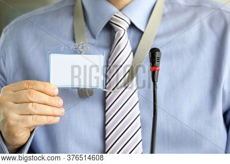 Man In Tie Shows Blank Badge Attending Seminar. Organization Seminars In Large Well-known Companies.