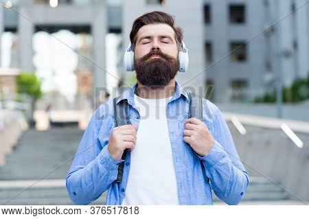 Modern Life. Man With Headphones Walking City Center. Listening Music. Handsome Hipster With Backpac