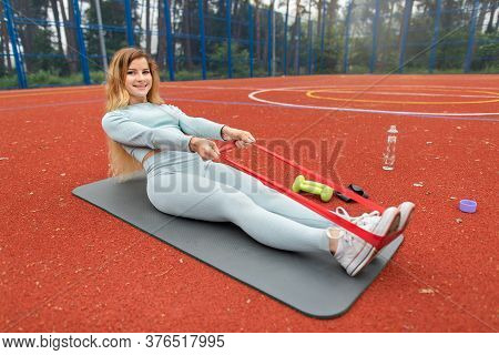 Fitness Girl In Gray Sportswear Workout With Fitness Elastic Band Outdoors On Red Coated Court. Spor