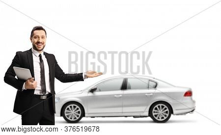 Car salesman holding a digital tabler and showing a silver new car isolated on white background