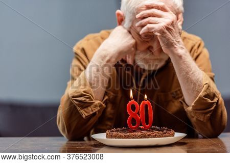 Depressed, Lonely Senior Sitting Near Birthday Cake With Number Eighty
