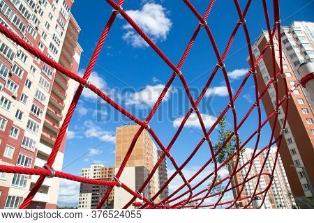 The Red Ropes In The Form Of Web Houses On The Background In The Backlight Of The Setting Sun. Child