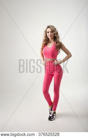 Attractive female in sporty shape wearing pink sportswear isolated on white background in studio. Full lenght portrait of fitness coach concept