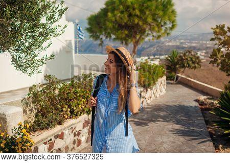 Santorini Traveler Explores Discovering Greek Architecture In Akrotiri. Girl Backpacker Walking Duri