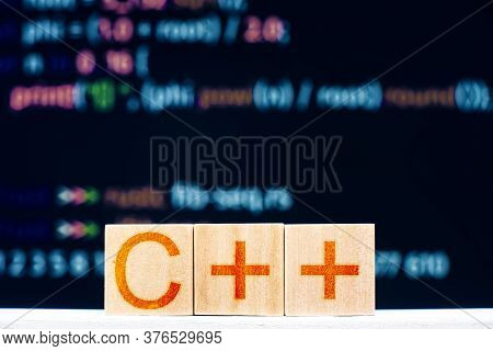 C ++ Concept. Wooden Blocks With The Inscription C ++ And Program Code On The Background