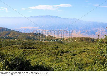 Lush Green Grasslands On A Plateau Overlooking The Arid Desert And The San Bernardino Mountains Beyo