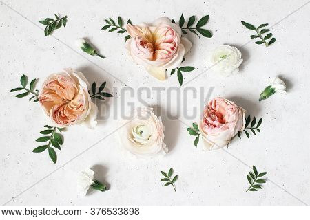 Floral Composition With Pink English Roses, Ranunculus And Green Leaves On White Concrete Table Back
