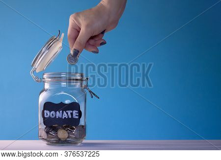 Hand Putting A Coin In A Glass Jar With Coins With A Chalk Donate Tag On A Blue Background. Donation
