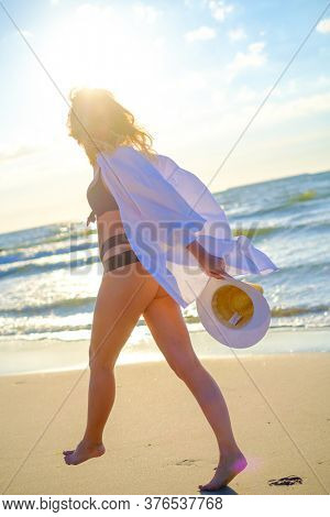 Side view of anonymous carefree female wearing bikini and shirt tiptoeing on wet sand along seashore and enjoying summer on sunny day