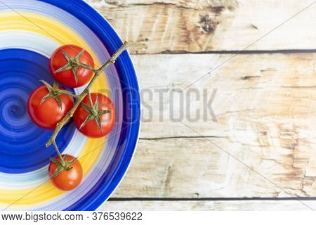 Cherry Tomatoes On Colorful Striped Plate And Brown Wooden Background