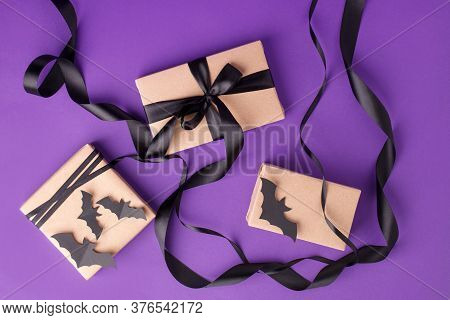Halloween Gift Boxes With Ribbon And Paper Decoration On Traditional Purple Background. Holiday, Bir