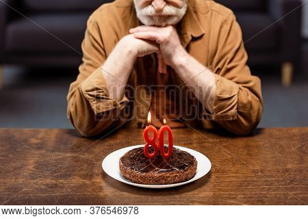 Cropped View Of Lonely Senior Man Leaning On Clenched Hands And Looking At Birthday Cake With Number