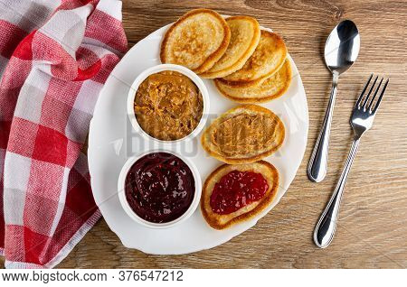 Checkered Napkin, Bowls With Raspberry Jam And Peanut Butter, Pancakes With Jam And Peanut Butter In