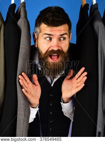 Shop Assistant Or Seller Hides Among Suits On Clothes Hangers.