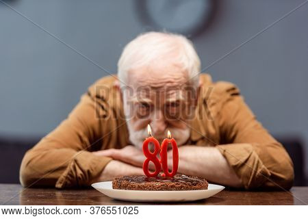 Selective Focus Of Lonely Senior Man Looking At Birthday Cake With Number Eighty
