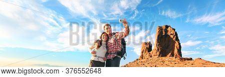 Selfie tourists taking photo with mobile phone at summit of mountain hike panoramic. Nature trek couple hikers hiking with backpacks in Europe panoramic banner.