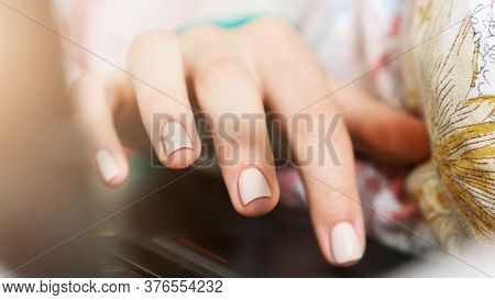 Young Woman Hand With White Manicure Types On Black Laptop Touchpad On Coloured Blanket In Early Mor