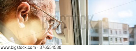 Senior Man In Glasses Looks Through Plastic Window With Open Vent At City Buildings Under Blue Sky C