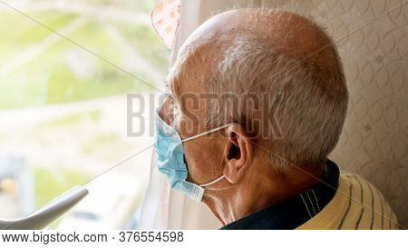 Aged Pensioner In Blue Disposable Mask Looks At Blurry Green Street Standing At Home Window Close Ba