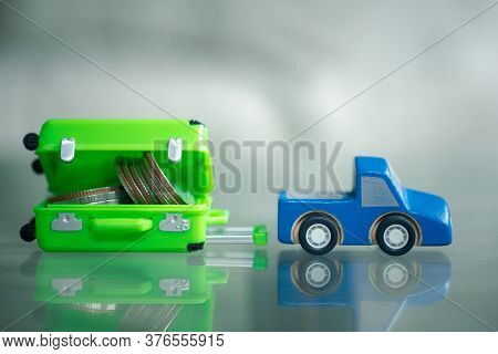 Miniature Blue Car Drag Of Coin In Miniature Suitcase. Concept Of Saving Money To Travel.