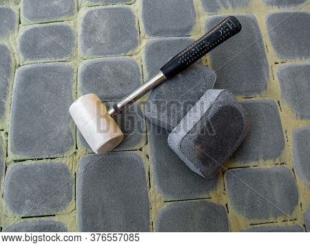White Rubber Mallet And Two Gray Paving Stones Lie On The Surface Of New Paving Slabs, Close-up. Con