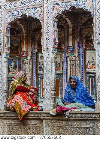 Nawalgarh, India - Dec 28, 2019: Women Dressed In Traditional Sari Sitting In Front Of A Haveli Of R