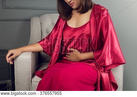 Asian Women Wear Silk Nightgown And Red Robe With A Stomach Ache In The Living Room At Night, Menstr