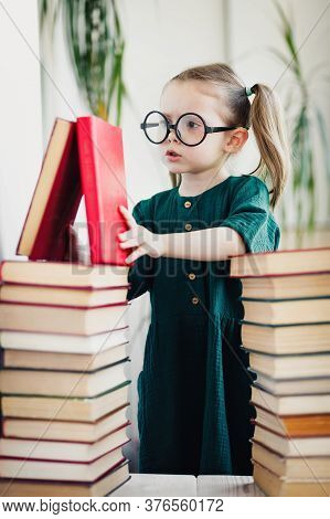 Child In Glasses With Pile Of Books, Vertical