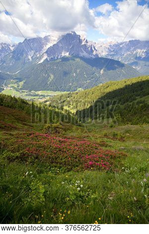 Forested Mountain Of Italian Dolomites, In The Background A Mountain Massif, Blue Sky With Clouds