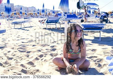 Little Girl In A Swimsuit On The Beach Plays, Smiles. Child 7 Years Old On The Equipped Beach Of Ita
