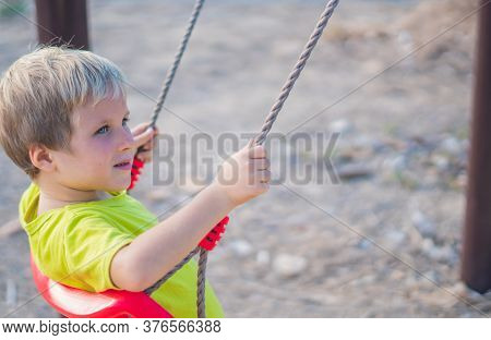 Happy Lovely Blond Little Boy Is Riding On A Swing, Playing Outside On Playground In The Park. Dayca