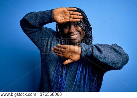 African american plus size woman with braids wearing casual sweater over blue background Smiling cheerful playing peek a boo with hands showing face. Surprised and exited