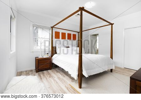 Bright And Cozy Modern Bedroom With En Suite, Large Windows And Cushions.