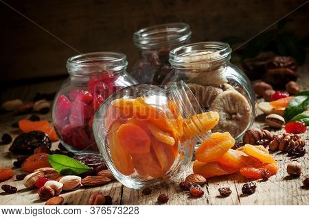 Dried Apricots In A Glass Jar On A Dark Wooden Background With Crumbled Nuts And Dried Fruits, Selec