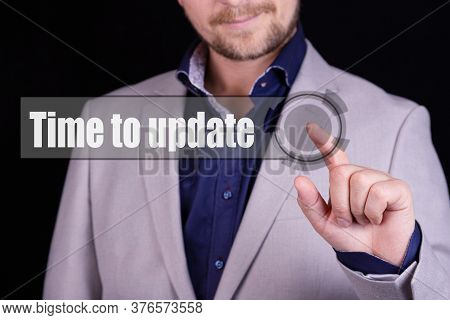 Businessman Presses A Button With The Text Time To Update. Business Concept.