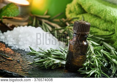 Rosemary Essential Oil Spa Composition With Sea Salt, Candles, Towels And A Fresh Branch Of Rosemary