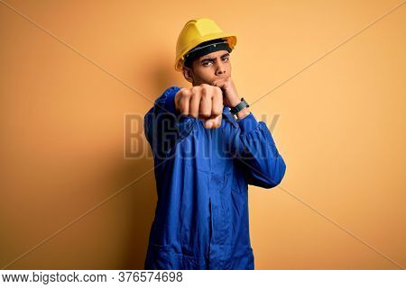 Young handsome african american worker man wearing blue uniform and security helmet Punching fist to fight, aggressive and angry attack, threat and violence