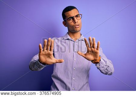 Handsome african american man wearing striped shirt and glasses over purple background Moving away hands palms showing refusal and denial with afraid and disgusting expression. Stop and forbidden.
