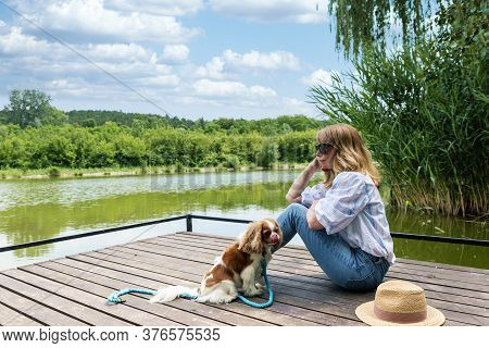 Full Length Shot Of Daydreaming Woman Sitting On The Pier Next To Her Puppy While Relaxing At The La
