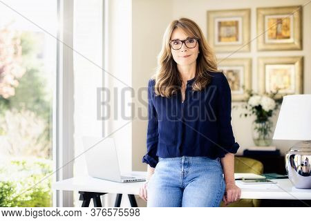 Portrait Shot Of Attractive Middle Aged Businesswoman Looking At Camera And Smiling While Standing A