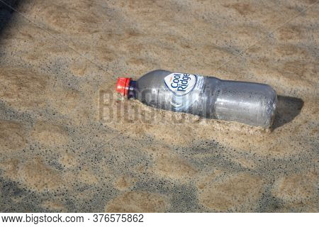 Perth, Western Australia - January 12, 2020: A plastic bottle with dirty foam in Swan River Perth.
