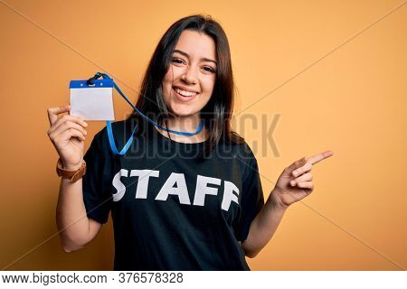 Young brunette worker woman wearing staff t-shirt as uniform showing id card very happy pointing with hand and finger to the side