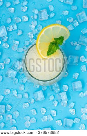 Lemonade Frappe With Round Slice Of Lemon And Mint On Blue Ice Background. Mojito Frappe Top View.