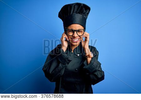 Young african american chef woman wearing cooker uniform and hat over blue background covering ears with fingers with annoyed expression for the noise of loud music. Deaf concept.